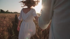 Follow me, young beautiful girl with her boyfriend runs across the field of - stock footage