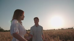 Follow me, young happy couple running through a field of Golden wheat at sunset - stock footage
