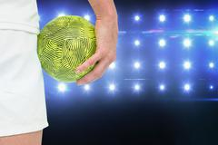 Sportswoman holding a ball against composite image of blue spotlight - stock photo