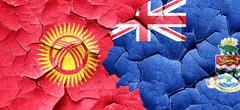 Kyrgyzstan flag with Cayman islands flag on a grunge cracked wal Stock Illustration