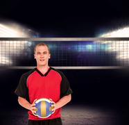 Sportsman holding a volleyball against view of spotlights - stock photo
