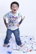 Young mischievous boy shouting with paint all over him against white background Stock Photos