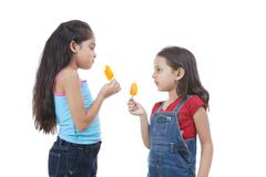 Girls holding ice lolly over white background Stock Photos
