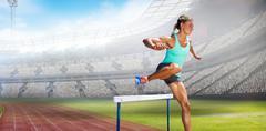 Sportswoman practising the hurdles against view of a stadium Stock Photos