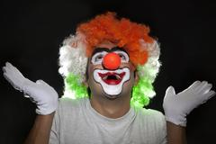 Smiling male joker looking up over black background Stock Photos