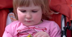 a Cute Toddler Girl in a Stroller Eating an Apple - stock footage