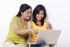 Mother and daughter using computer together over white background Stock Photos