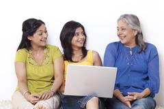 Girl sitting with her mother and grandmother shopping online Stock Photos