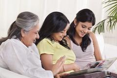 Multi-generation family looking at photo album Stock Photos