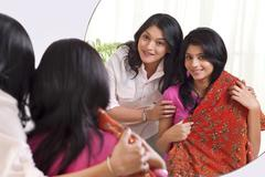 Smiling girl with her mother trying on traditional outfit Stock Photos
