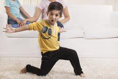 Little boy dancing with family in the background Stock Photos