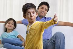 Boy acting in front of father and sister Stock Photos