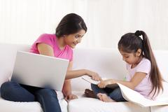 Happy young woman assisting her daughter in drawing Stock Photos
