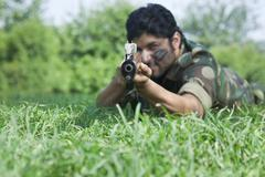 Soldier aiming with rifle while lying on grass Stock Photos