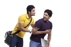 Young man hiding his cell phone from his curious friend Stock Photos