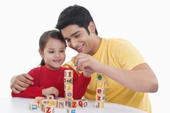 Smiling father assisting girl in playing block game Stock Photos