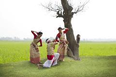 Bihu man playing on a pepa while Bihu women dance to his tune Stock Photos