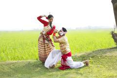 Bihu man blowing on a pepa while Bihu woman dances to his tune Stock Photos