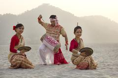 Bihu women dancing with brass plates as Bihu man plays on a dhol Kuvituskuvat