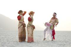 Bihu women dancing as Bihu man plays on a dhol Kuvituskuvat