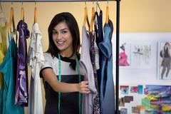 Female stylist selecting clothes on rack in studio Stock Photos