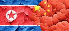 North Korea flag with China flag on a grunge cracked wall Stock Illustration