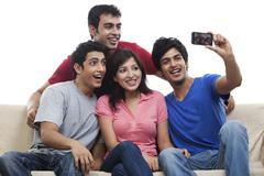 Friends clicking self photograph over white background Stock Photos