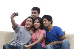 Young friends taking self picture over white background Stock Photos