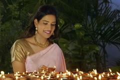 Young woman arranging diyas Stock Photos