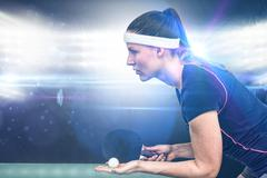 Composite image of female athlete playing table tennis against spotlight - stock photo