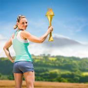 Woman posing with trophy against country scene - stock photo