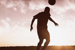 Football player hitting header against sun shining Stock Illustration
