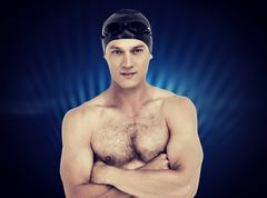 Portrait of swimmer posing with arms crossed against black glowing design - stock photo