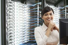 Portrait of smiling business woman sitting in server room Kuvituskuvat