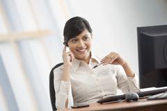 Female executive talking on a blue-tooth headset Stock Photos
