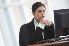Mature businesswoman looking at computer with concentration Stock Photos