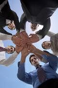 Business people stacking hands to show unity Stock Photos