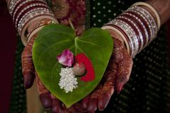 Close-up of Indian bride's hand holding areca nut , flower petal and rice on Stock Photos