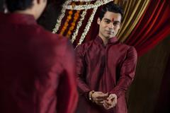 Mirror reflection of young Indian bridegroom getting dressed Stock Photos