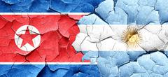 North Korea flag with Argentine flag on a grunge cracked wall Stock Illustration