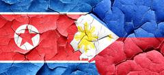 North Korea flag with Philippines flag on a grunge cracked wall - stock illustration