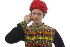 Male dandiya dancer talking on a mobile phone Stock Photos