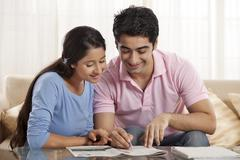 Smiling young couple solving crossword newspaper together Stock Photos
