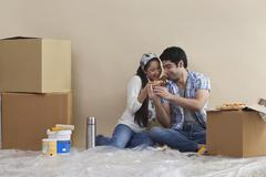 Happy young couple sharing pizza at their new home Stock Photos