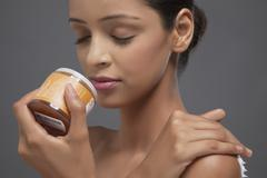 Close-up of young woman smelling scrub bottle Stock Photos