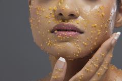Young woman applying scrub on face Stock Photos