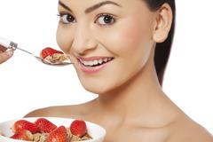 An attractive young woman eating cornflakes with strawberries Stock Photos
