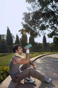 Young man with towel round shoulders drinking water after sport activities Stock Photos