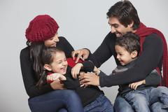 Happy playful family sitting over grey background Stock Photos