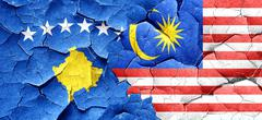 Kosovo flag with Malaysia flag on a grunge cracked wall - stock illustration